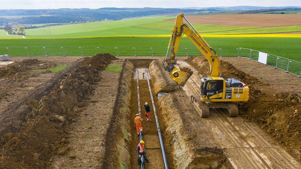 Bauarbeiter verlegen Stromkabel in der Erde.