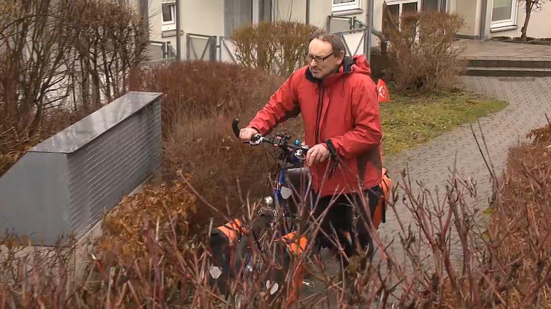Ein Mann schiebt sein voll bepacktes Fahrrad.