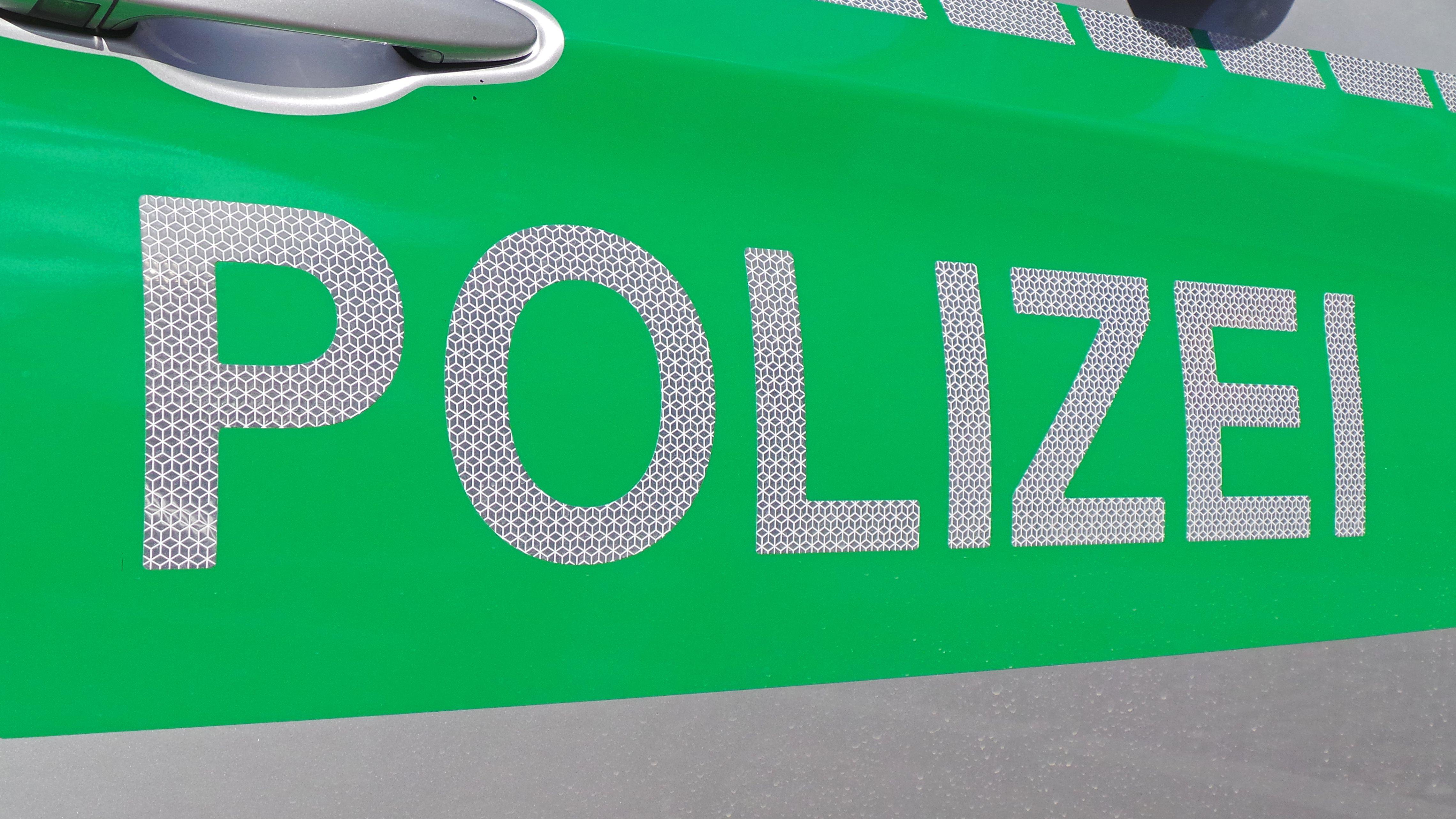 Schriftzug Polizei auf der Seite eines Polizeiautos.