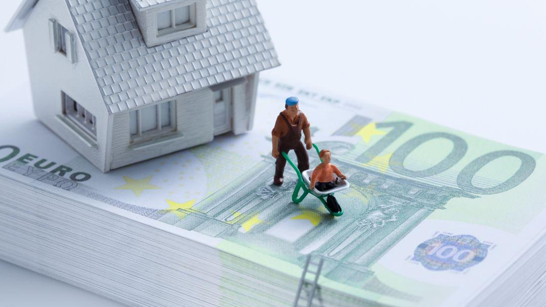 Hausmodell und Figuren auf Stapel Euroscheine