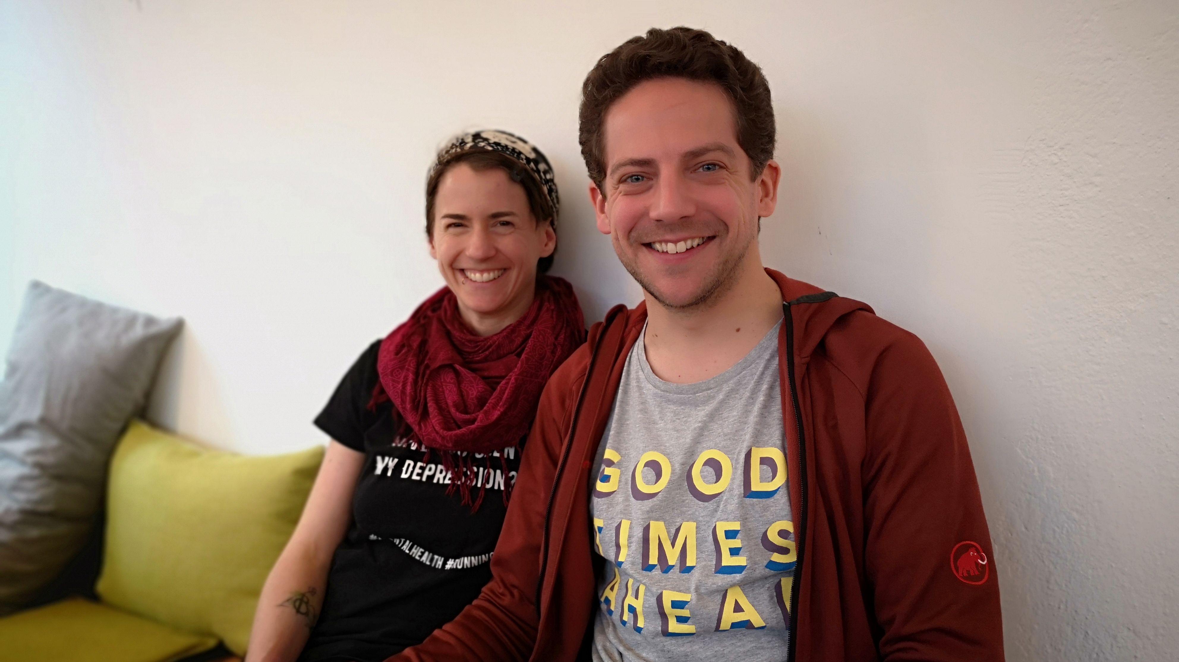 Die Cafébetreiber Dominique de Marné und Lasse Münstermann sitzen nebeneinander auf einer Bank und lächeln in die Kamera.