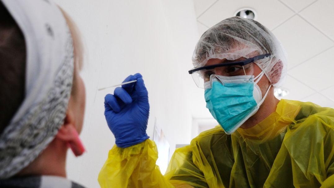 Ein Mitarbeiter des Deutschen Roten Kreuzes testet eine Frau auf das Coronavirus