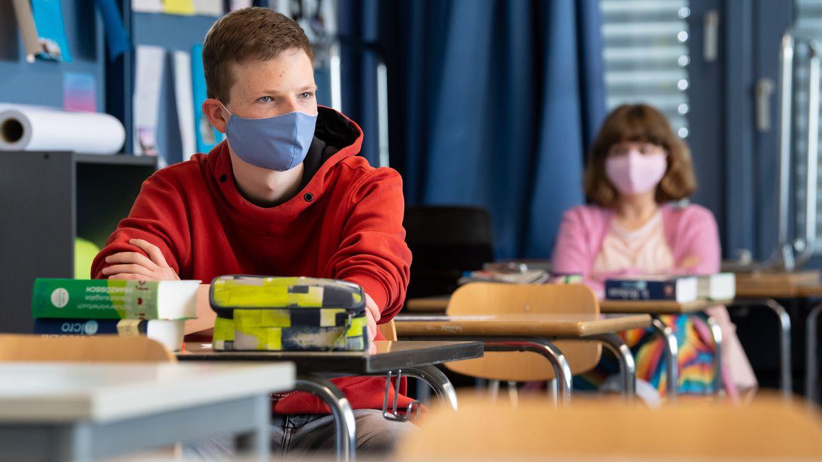 Schüler und Schülerinnen nehmen am Unterricht teil und tragen dabei Mundschutz.