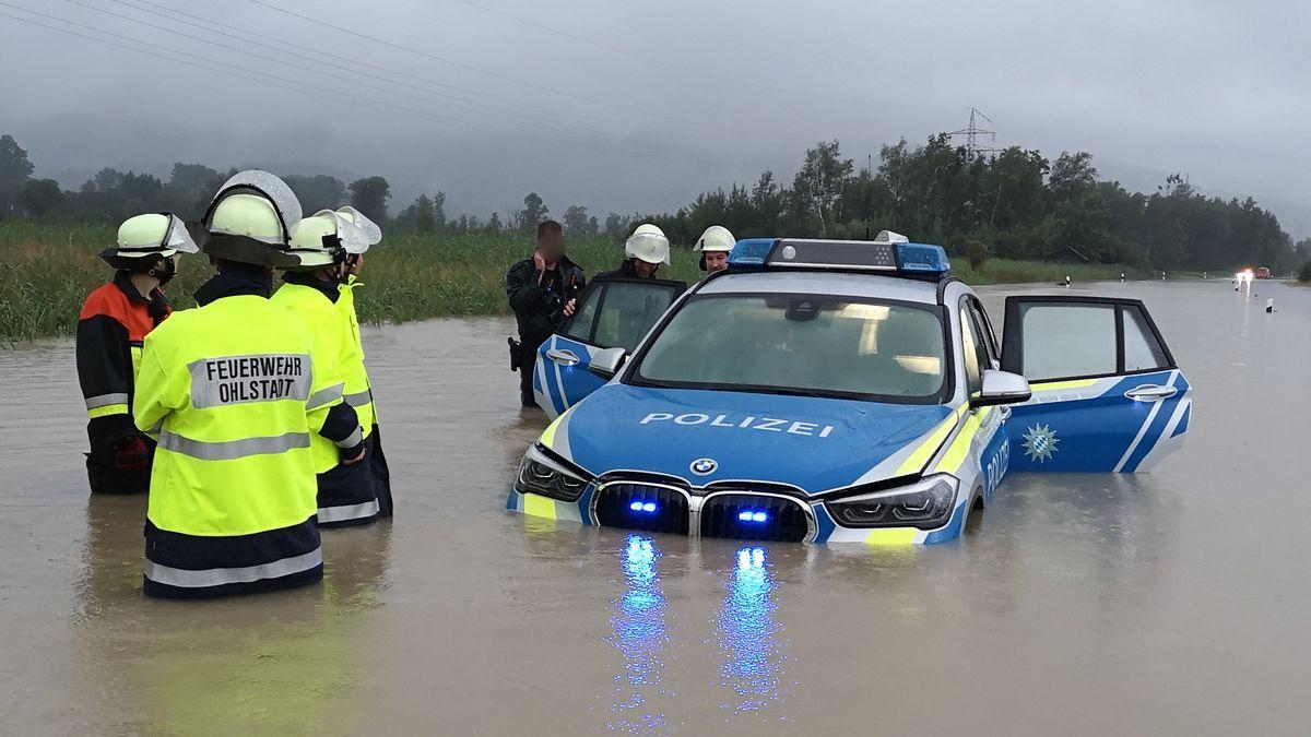 Ein Polizeiauto steht bis knapp unter die Motorhaube im Wasser. Um das Fahrzeug herum stehen Polizisten und Feuerwehrleute.