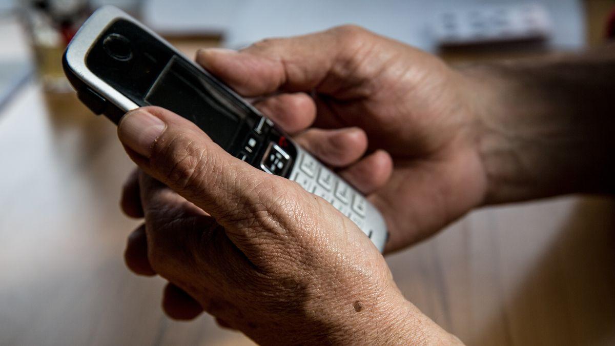 Ein Mann hält ein Telefon in der Hand