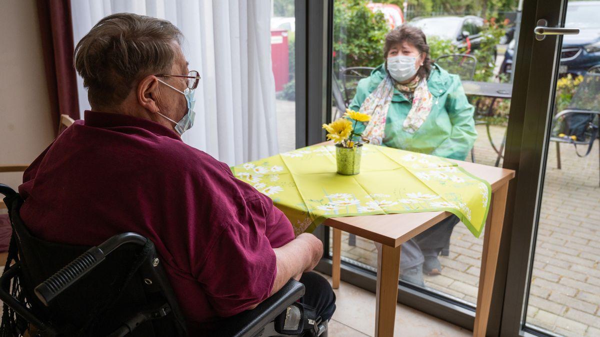 Pflegebedürftiger im Rollstuhl schaut durch die Glastüre nach draußen zu seiner Frau