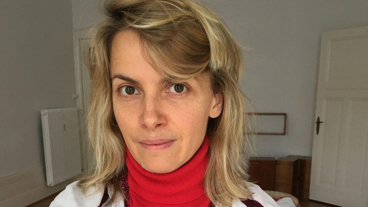 Portrait von Kunsthistorikerin Julia Voss in einem Altbau mit rotem Rollkragenpullover