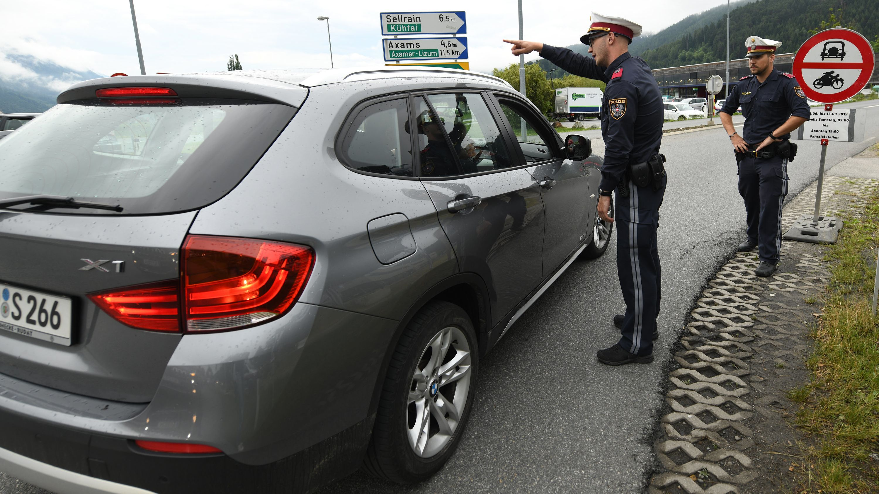 Ein graues SUV wird von Polizisten angehalten. Ein Polizist deutet auf die Richtung in die das Auto fahren soll.