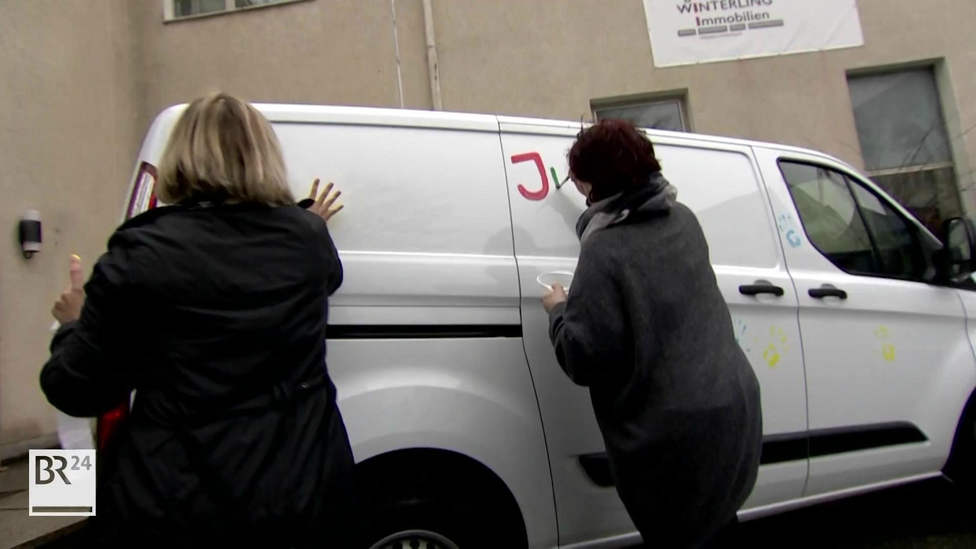 Zwei Frauen bemalen einen weißen Kleinbus.