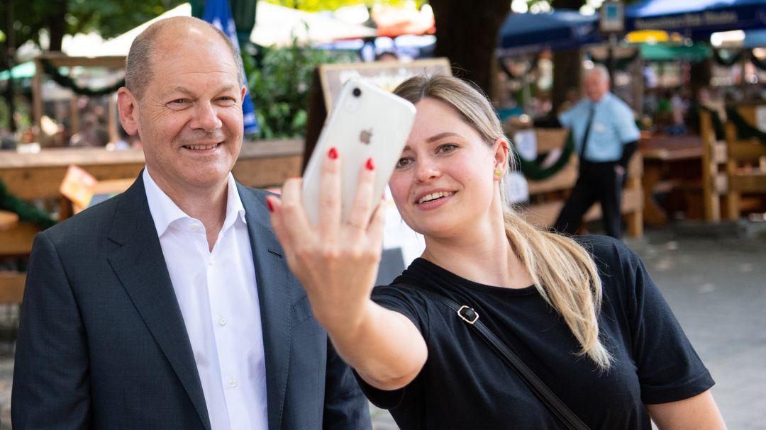 Olaf Scholz, SPD-Kanzlerkandidat und Bundesfinanzminister, macht auf dem Viktualienmarkt ein Selfie mit einer Frau.