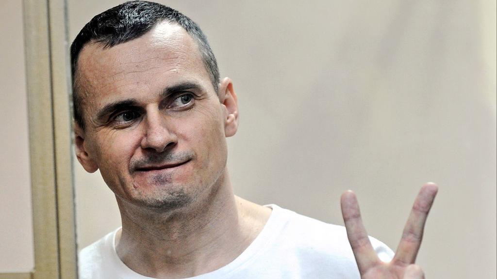 Russland, Rostow am Don: Der inhaftierte Filmemacher Oleg Senzow aus der Ukraine macht in einem Gericht mit der linken Hand das Victory-Zeichen, während sein Urteil verkündet wird.