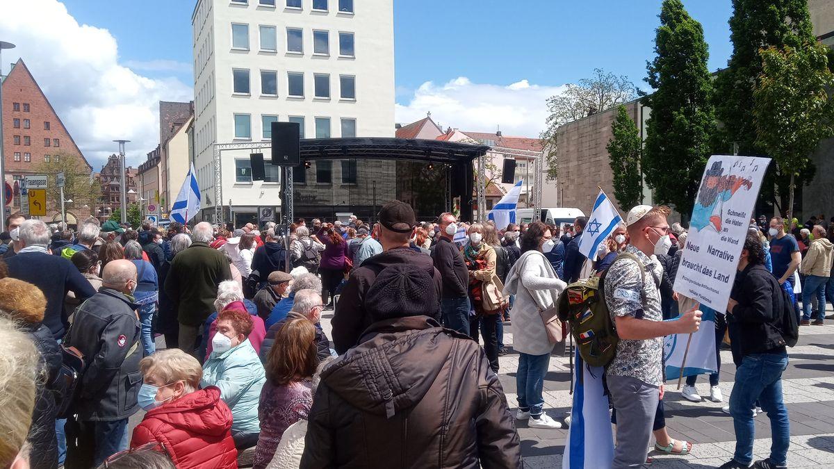 Menschen stehen auf einem Platz, manche haben Israel-Flaggen.