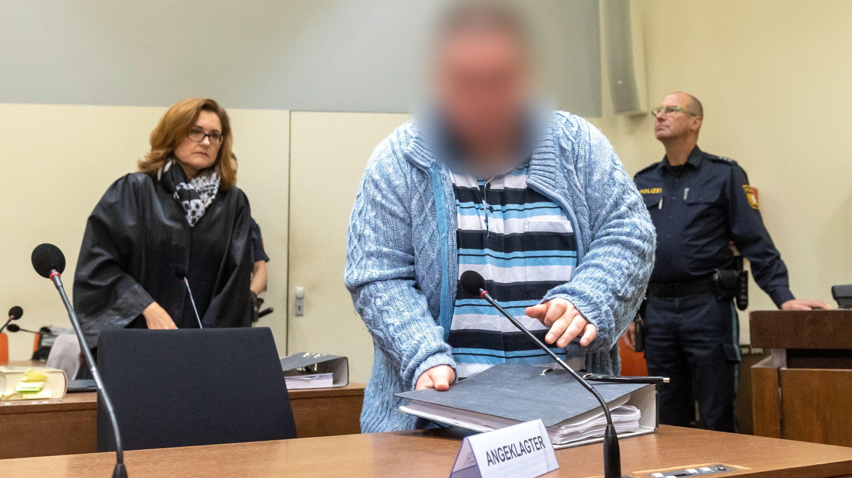 Der Angeklagte steht zum Prozessauftakt an seinem Platz im Gericht. Links steht seine Anwältin Birgit Schwerdt.