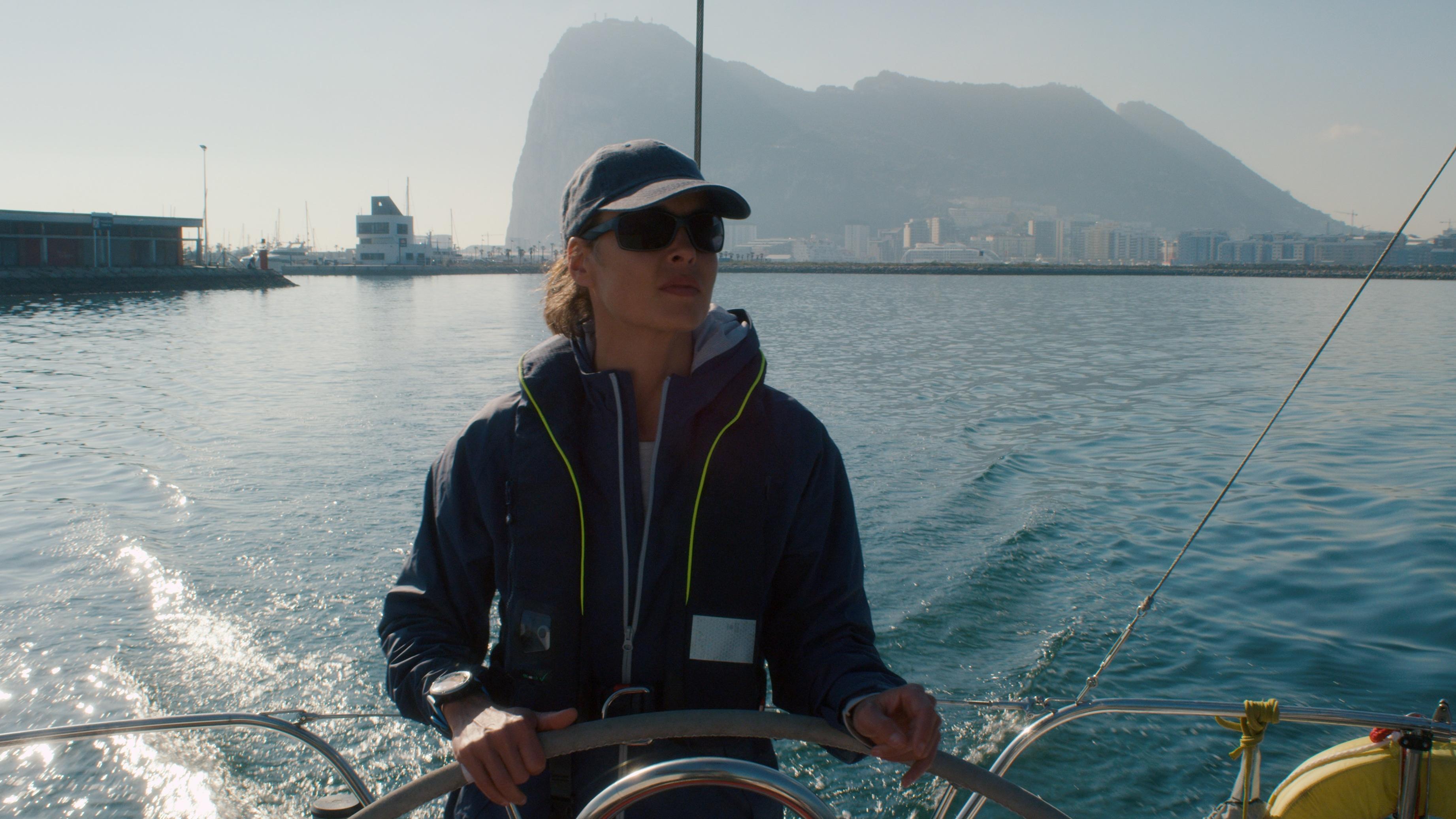 """Eine Frau fährt mit einem Boot raus auf das Meer, im Hintergrund der Berg von Gibraltar, Filmstill aus """"Styx""""."""