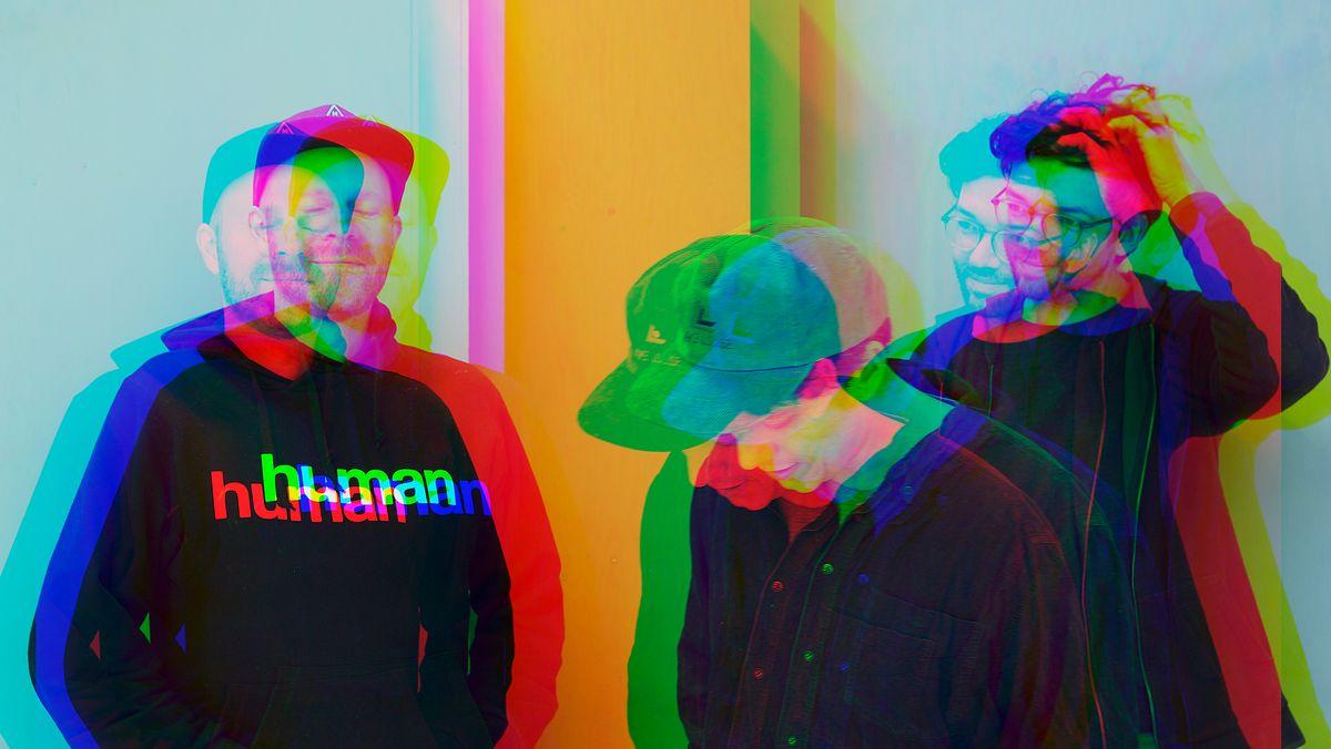 Drei junge Männer stehen in einer losen Gruppe zusammen