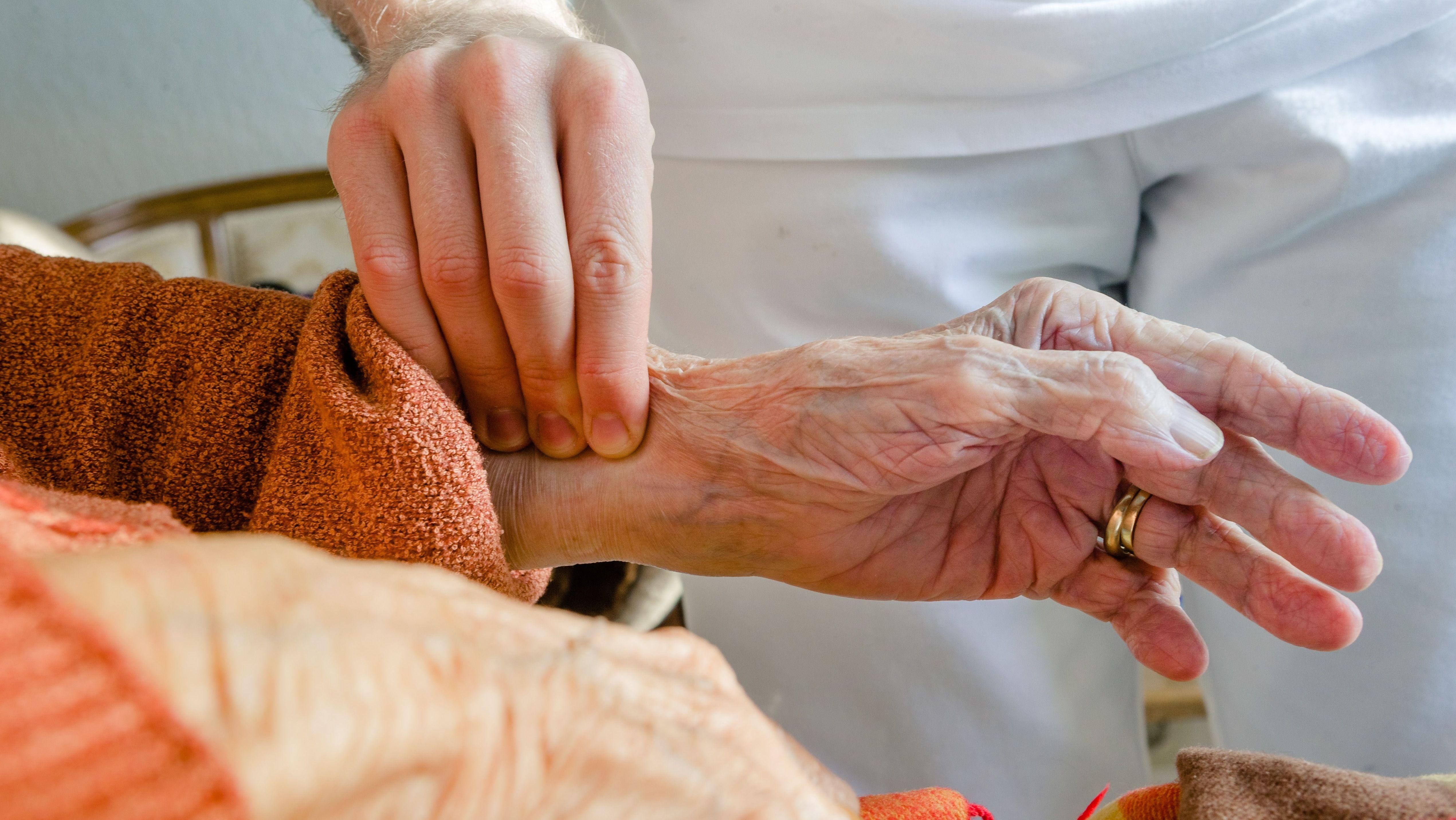 Ein Altenpfleger misst bei einer Bewohnerin den Puls