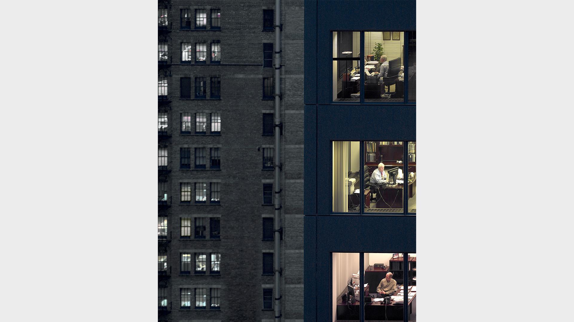 Ein blaues Hochaus in Chicago, in drei übereinander liegenden Büros brennt Licht und man kann drei Männern bei der Arbeit am Schreibtisch beobachten.