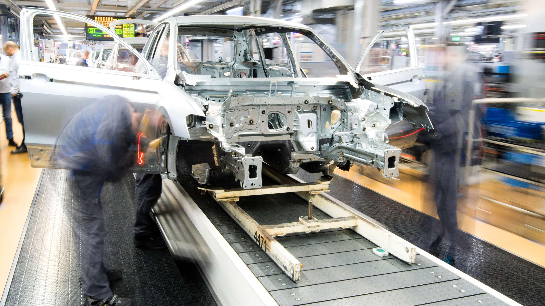 Mitarbeiter montieren Kotflügel an einen Volkswagen Golf VII im Karosseriebau im VW-Werk
