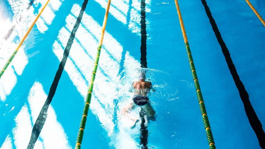 Ein Mann schwimmt in einem Hallenbad