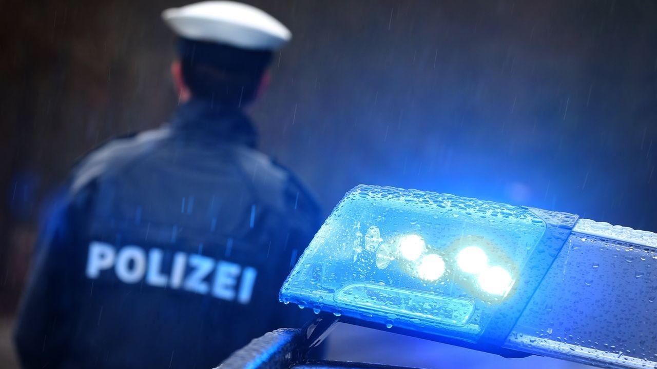 Ein Polizist steht im Regen vor einem Streifenwagen dessen Blaulicht aktiviert ist (Symbolbild)