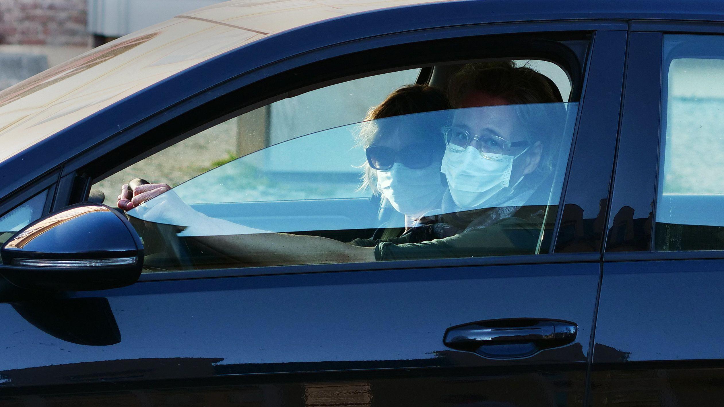 Autofahrerin mit Maske. Eine Beifahrerin trägt auch eine Maske. (Symbolbild)