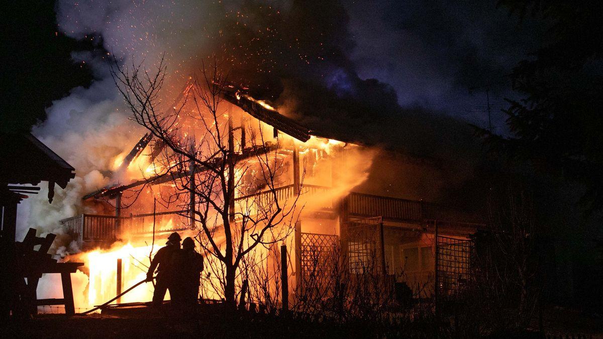 Ein lichterloh brennendes Wohnhaus in der Nacht, davor die Silhouetten von zwei Feuerwehrmännern.