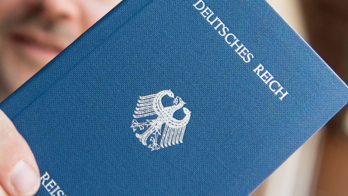 """Symbolbild: Ein Mann hält ein Heft mit dem Aufdruck """"Deutsches Reich Reisepass"""" in der Hand"""