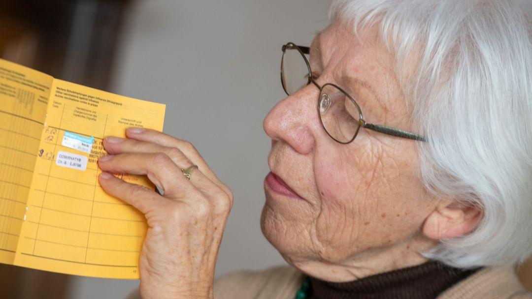 Seniorin blickt in ihren Impfpass