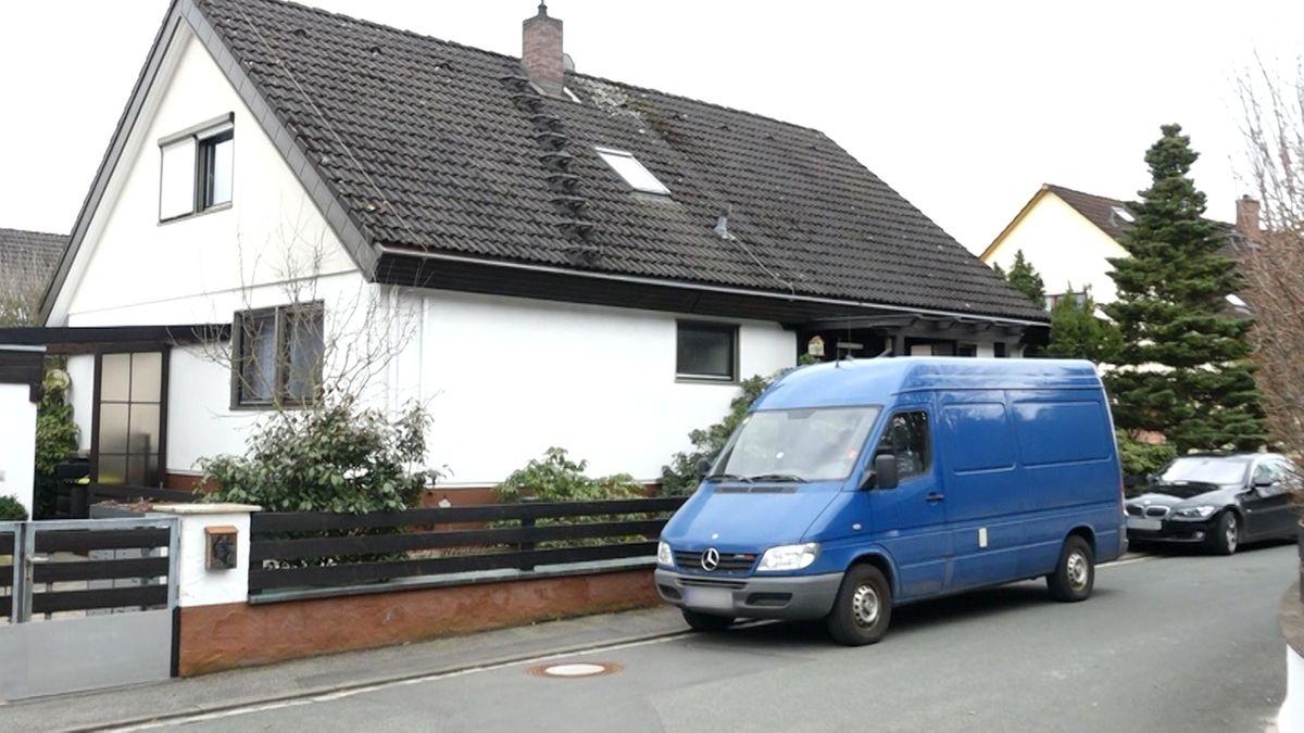 Vor einem Haus parkt ein blaues Kastenfahrzeug.