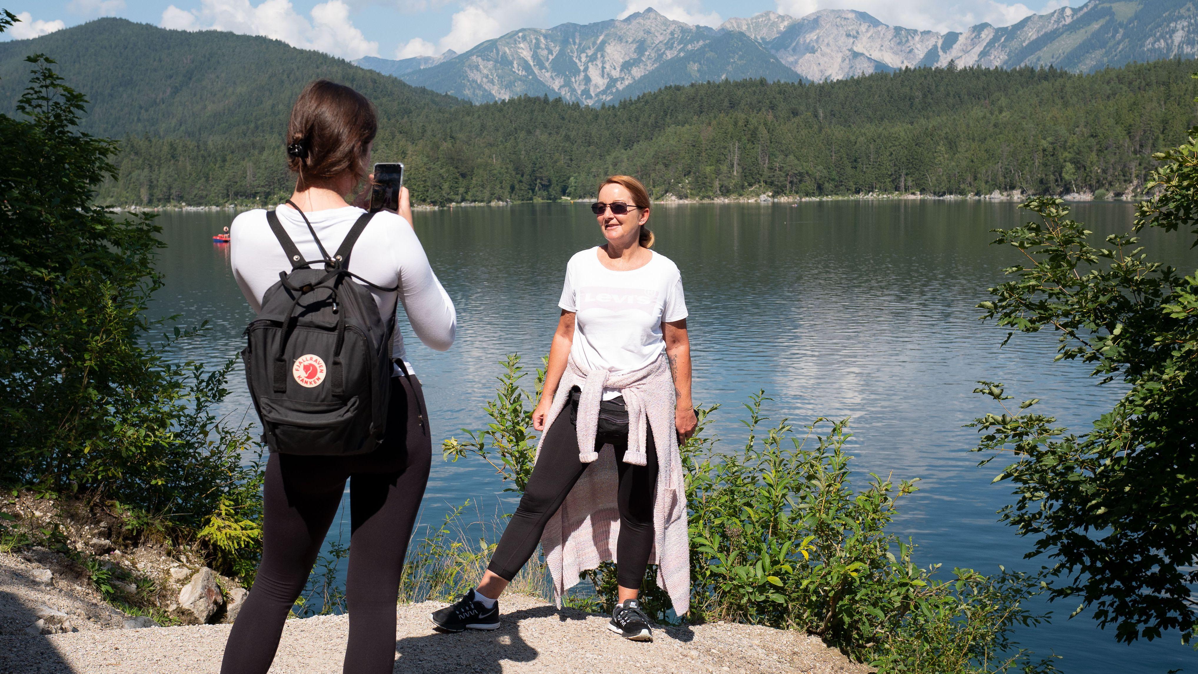 Eine junge Frau fotografiert ihre Mutter am Ufer des Eibsees, im Hintergrund das Wettersteingebirge.