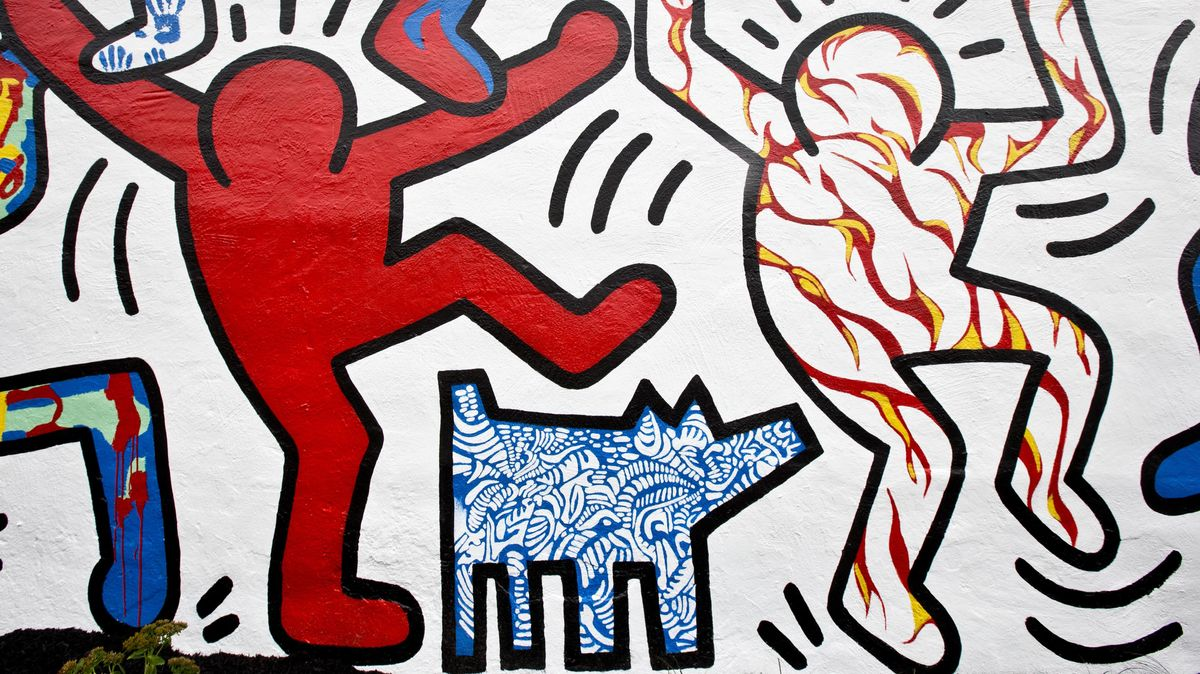 """Detail der neu restaurierten Wandmalerei von 1987 """"We The Youth"""" by artist Keith Haring. Abstrakte Darstellung von zwei Menschen, die auf ihren Schultern andere Personen tragen, eine Art Tanz machen, der eine hebt ein Bein, darunter steht ein Hund."""