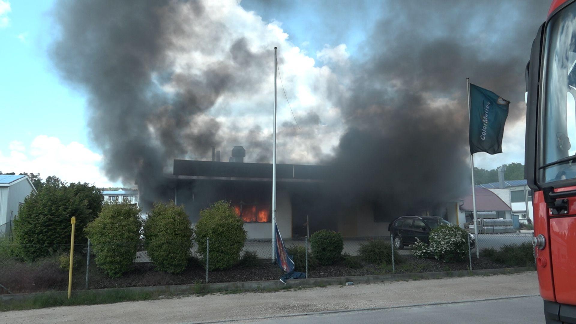 Ein brennendes Gebäude, schwarzer Rauch steigt aus Fenstern und Türen auf.
