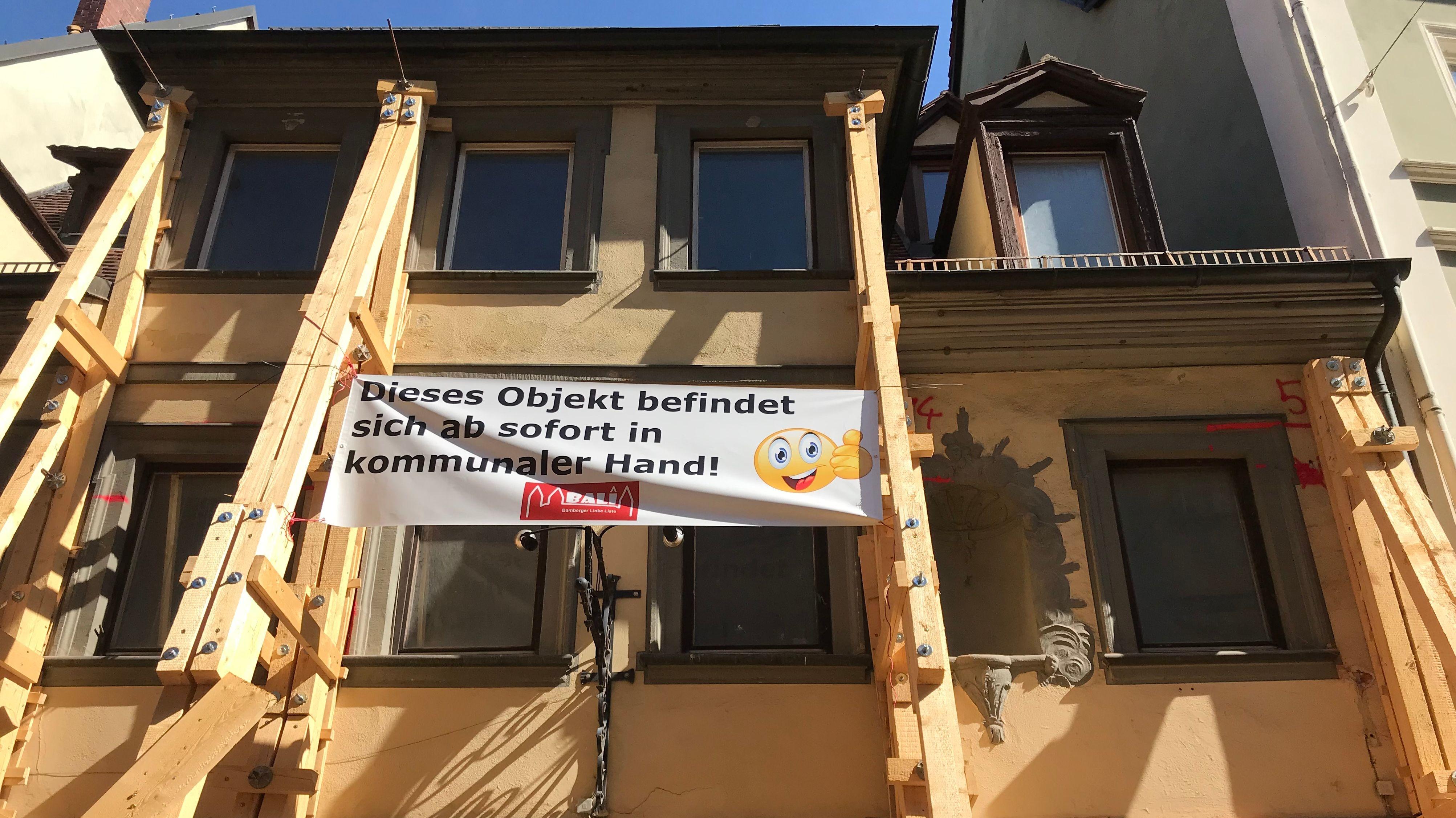 Einsturzgefährdetes Haus mit Plakat und Stützsäulen