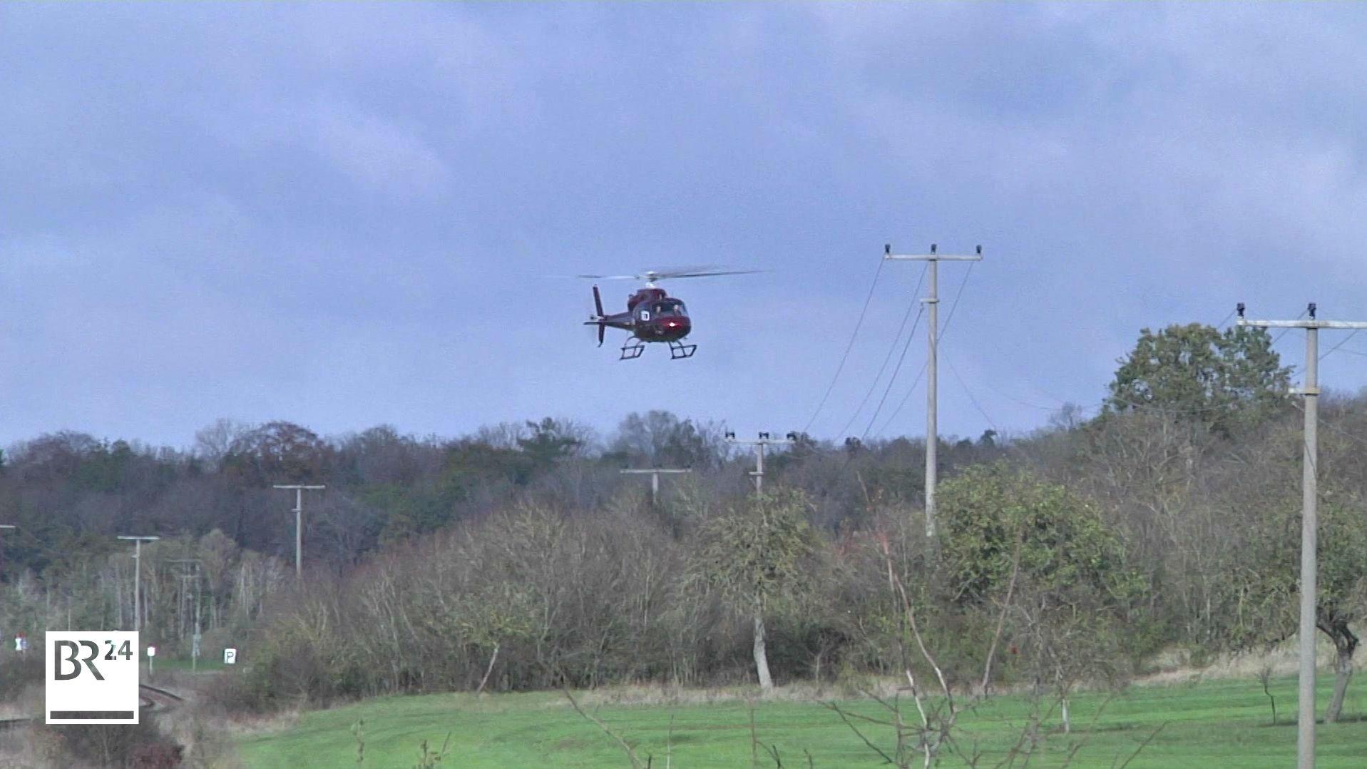 Hubschrauber fliegt über Stromleitungen