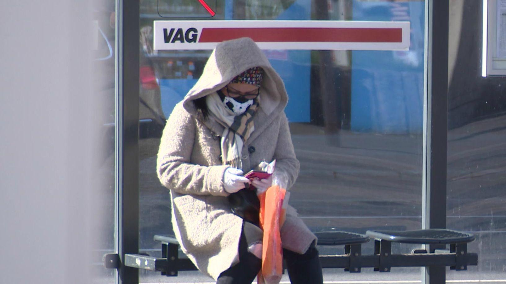 Frau mit Schutzmaske und Handschuhen wartet an Bushaltestelle der VAG in Nürnberg.