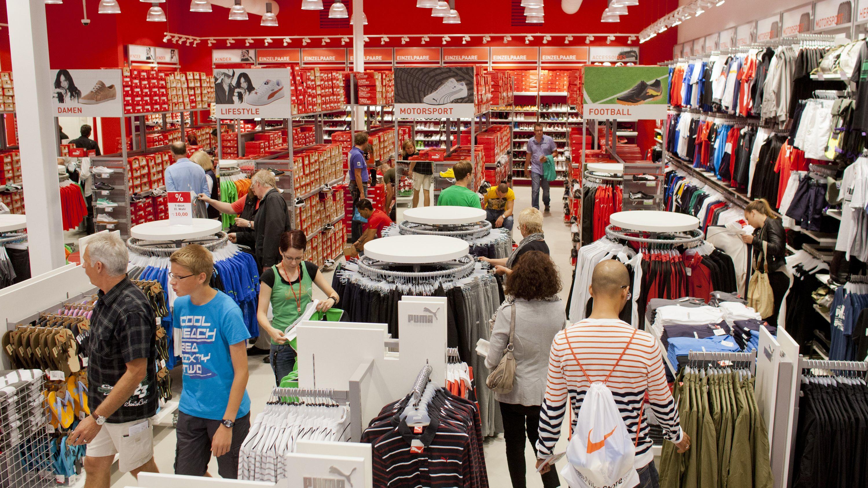 Kunden schauen in einem Outlet-Laden Waren an.