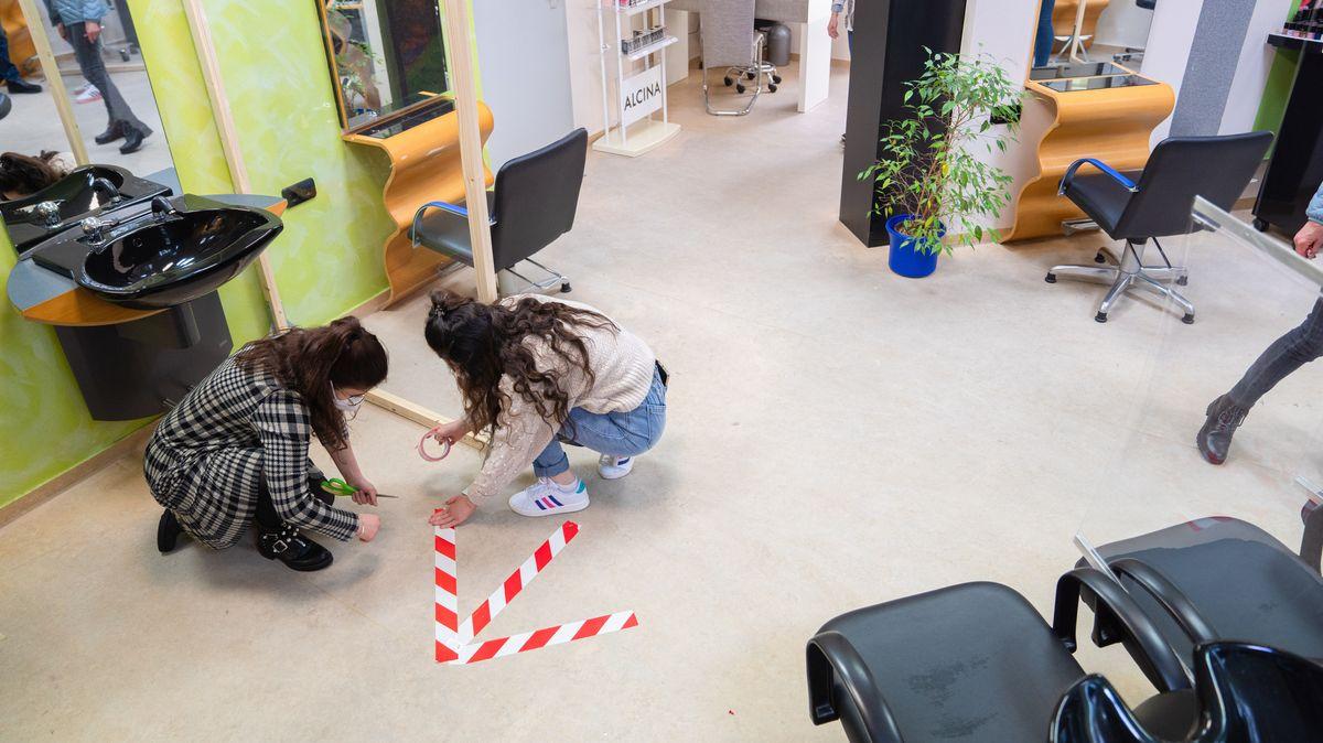 """Die Friseurinnen Sandra (l) und Athraa (r) kleben im Friseursalon """"Extra Locke"""" in Schweinfurt Markierungen auf den Boden."""