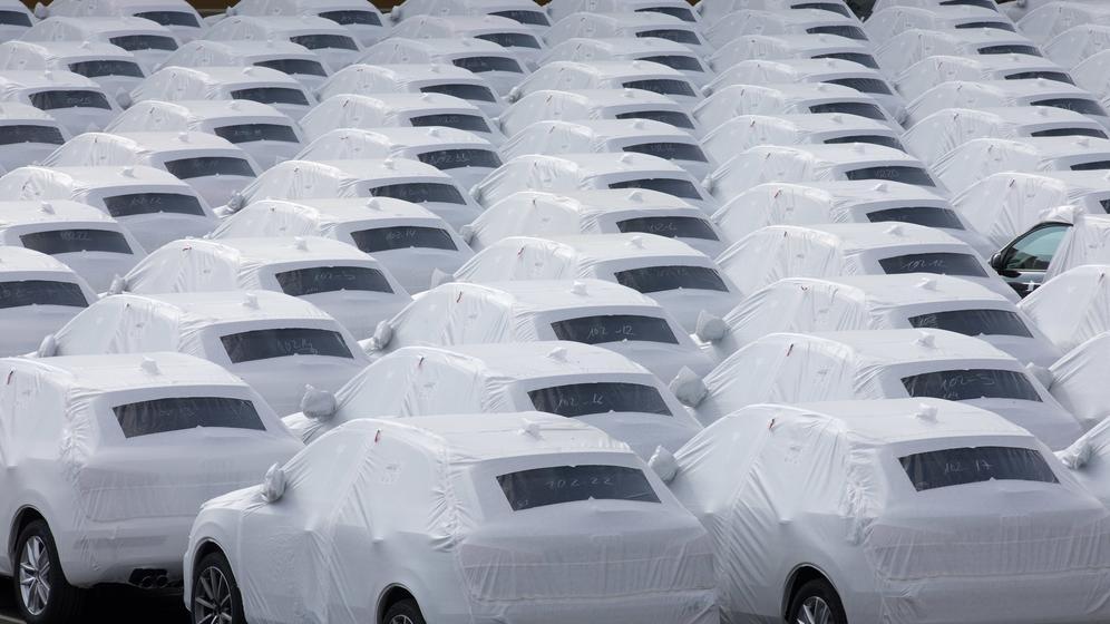 Neuwagen stehen verhüllt auf einem Parkplatz   Bild:dpa/Jörg Sarbach