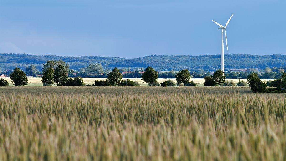 Ein Windrad steht in einer hügeligen Landschaft.