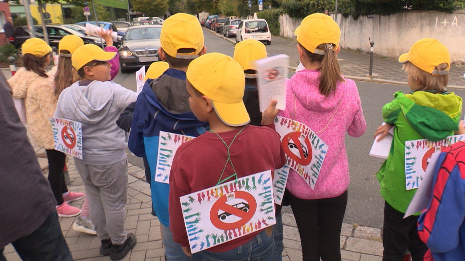 Grundschüler verteilen vor der Nürnberger Sperberschule Flyer an Eltern
