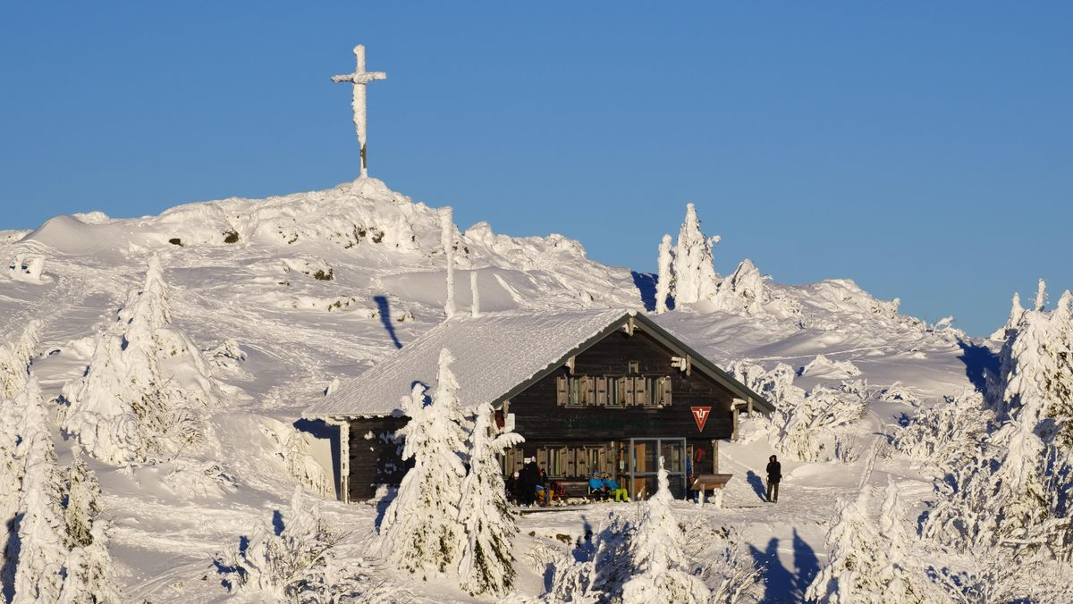 Auf dem Großen Arber: das Gipfelkreuz über Zwieseler Hütte bei Schnee