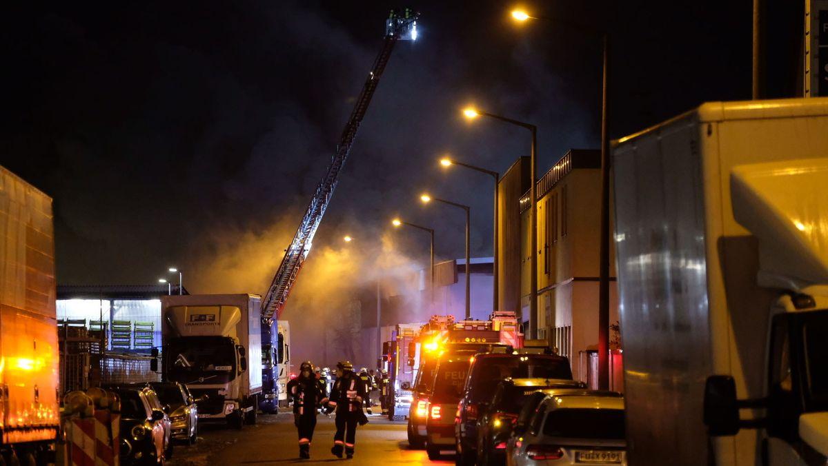 Feuerwehrauto mit Drehleiter und andere Einsatzfahrzeuge und Feuerwehrleute in einer Straße, im Hintergrund qualmt es.
