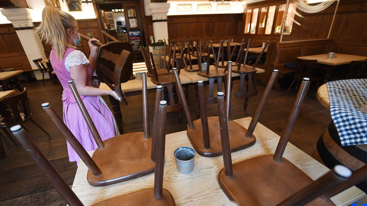 Eine Bedienung stellt in einem Wirtshaus in Garmisch-Partenkirchen die Stühle auf die Tische.