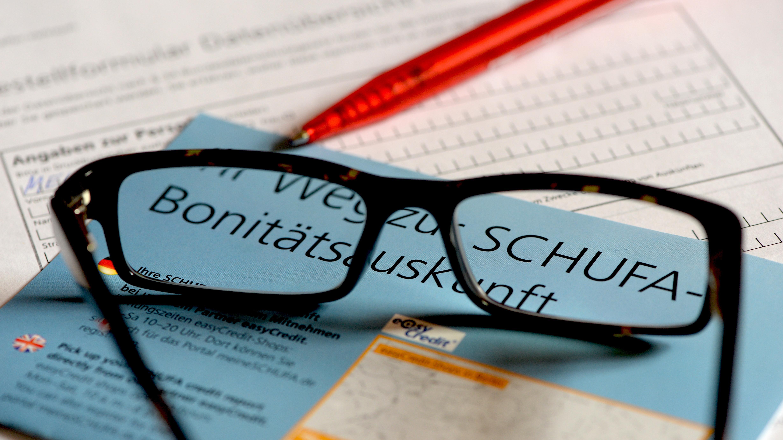 Brille und ein Kugelschreiber auf Antrag für Schufa-Auskunft