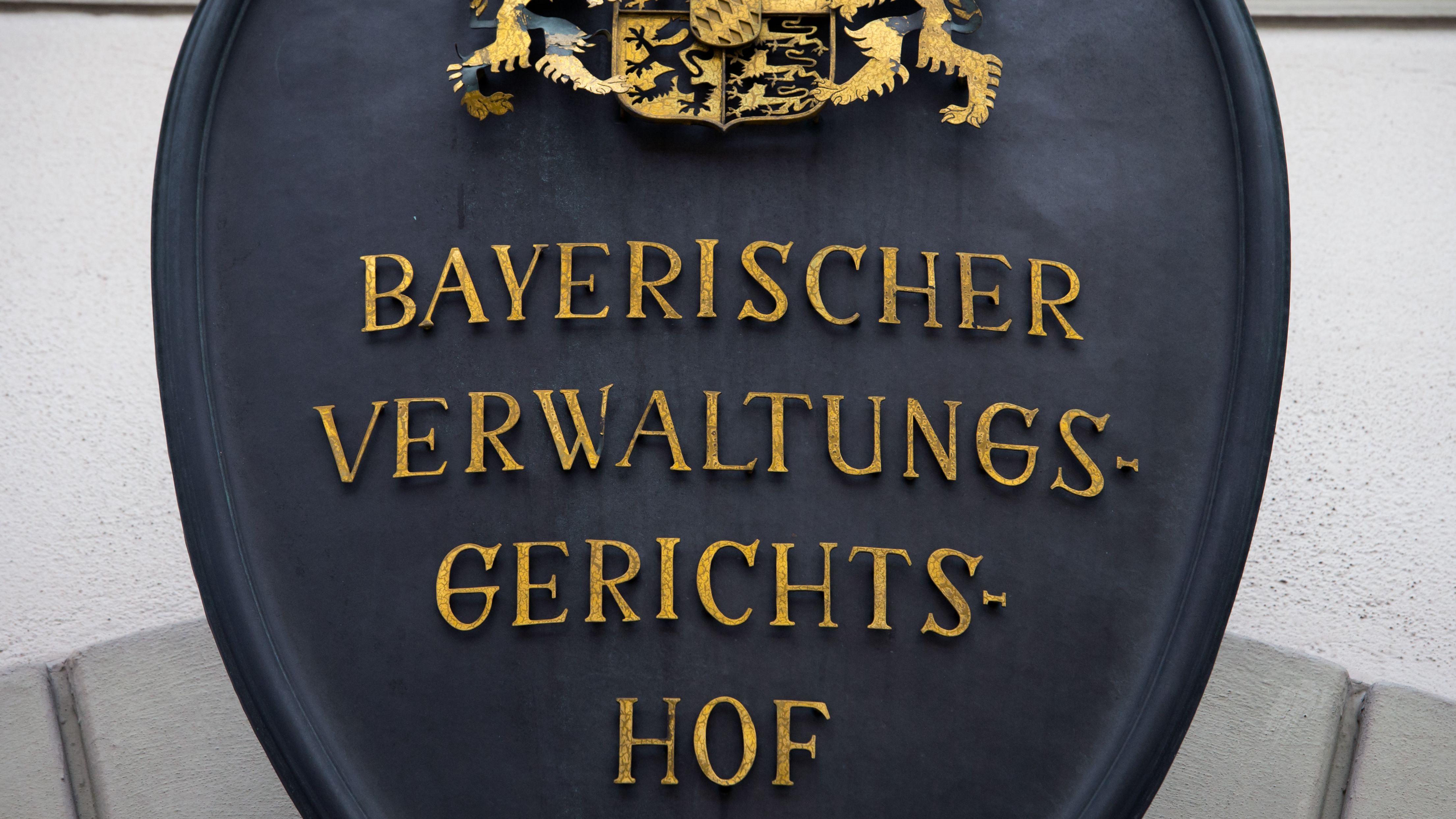 """Ein Schild mit der Aufschrift """"Bayerischer Verwaltungsgerichtshof"""" hängt  an der Fassade des bayerischen Verwaltungsgerichtshof in München."""