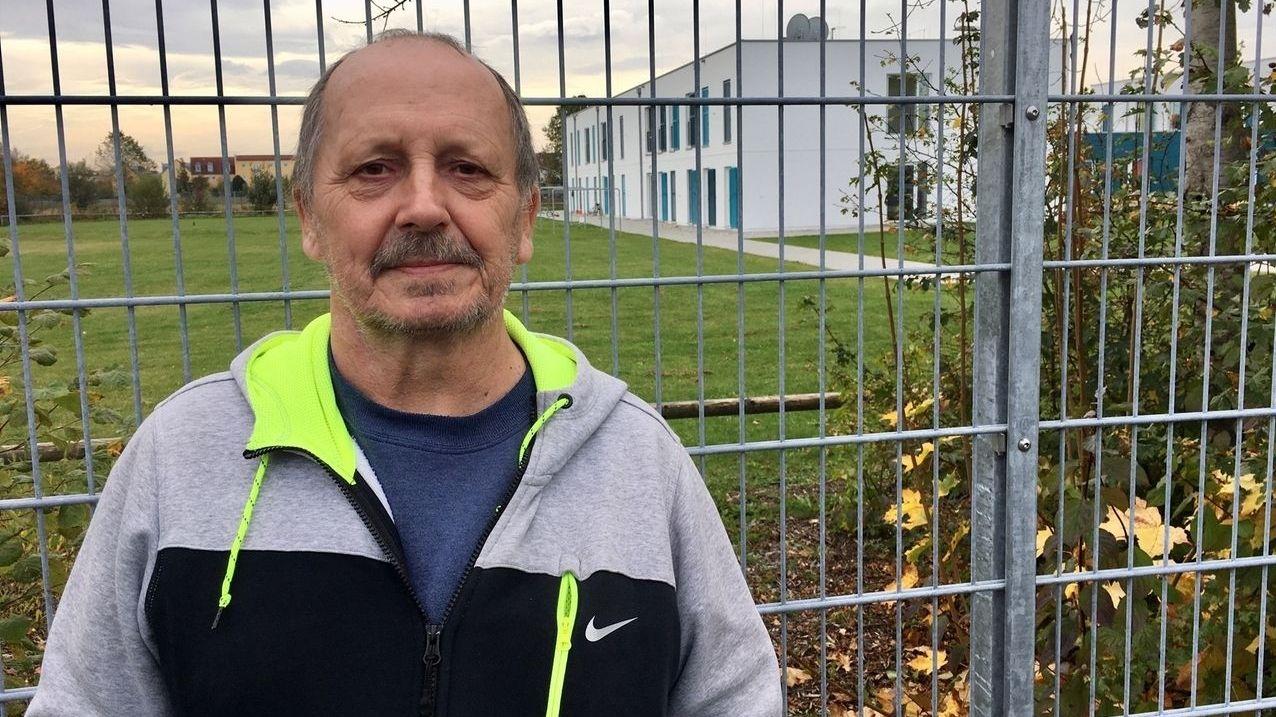 Guido Bucholtz steht in Neuperlach-Süd vor der Flüchlingsunterkunft, die durch eine Mauer von einer Wohnsiedlung getrennt ist.
