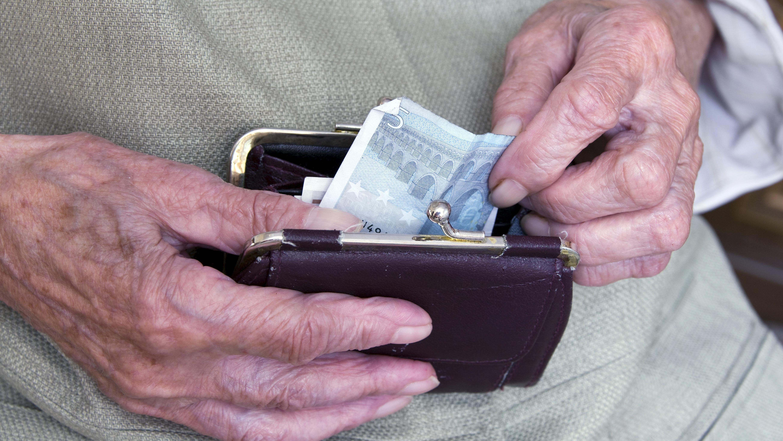 Seniorin greift nach Geldschein im Geldbeutel