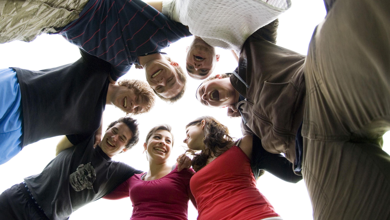 Sieben Freunde im Teenager-Alter bilden einen Kreis und umarmen sich