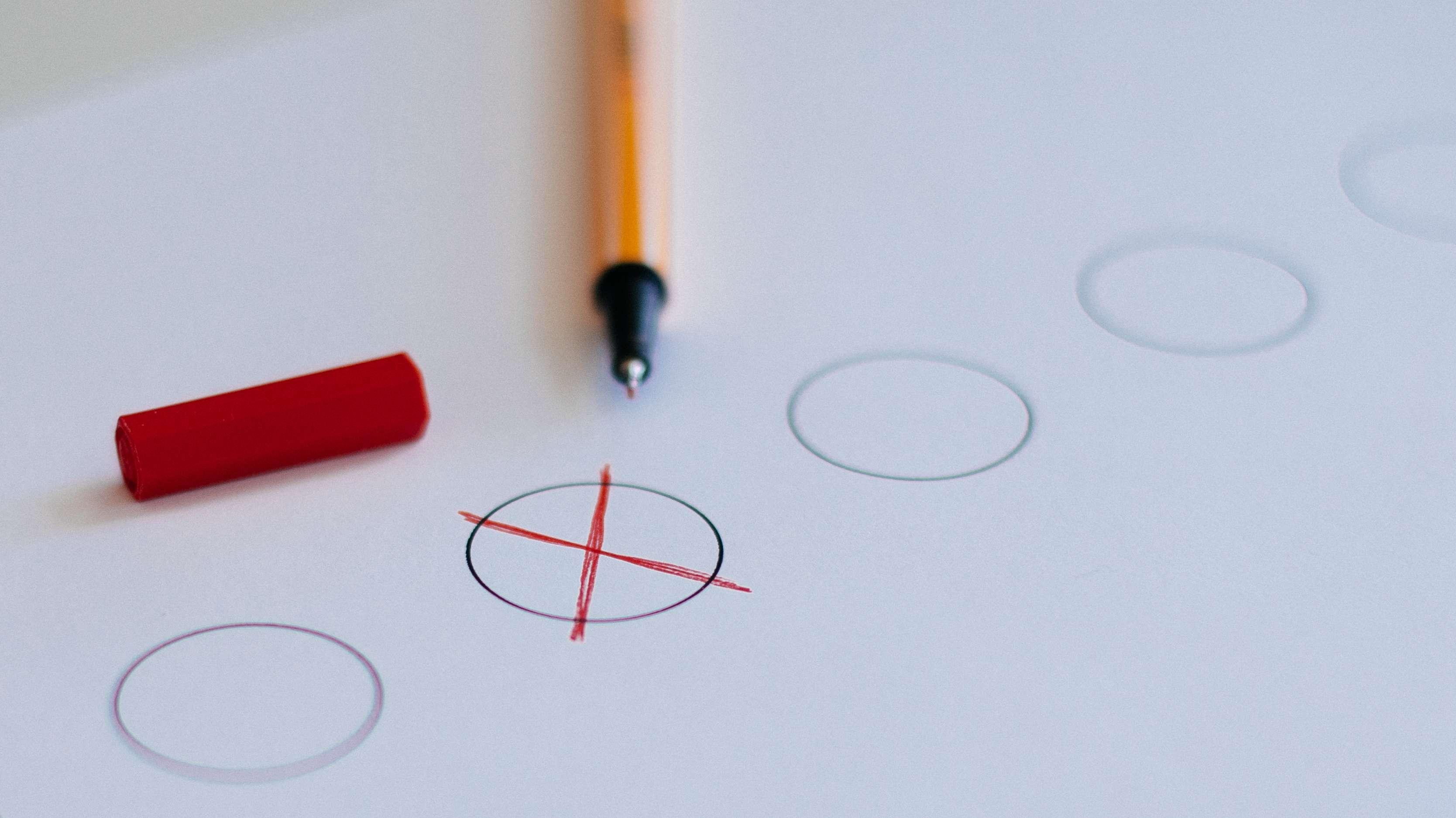 Rotes Kreuz in einem Kreis als Symbolbild fürs Wählen.