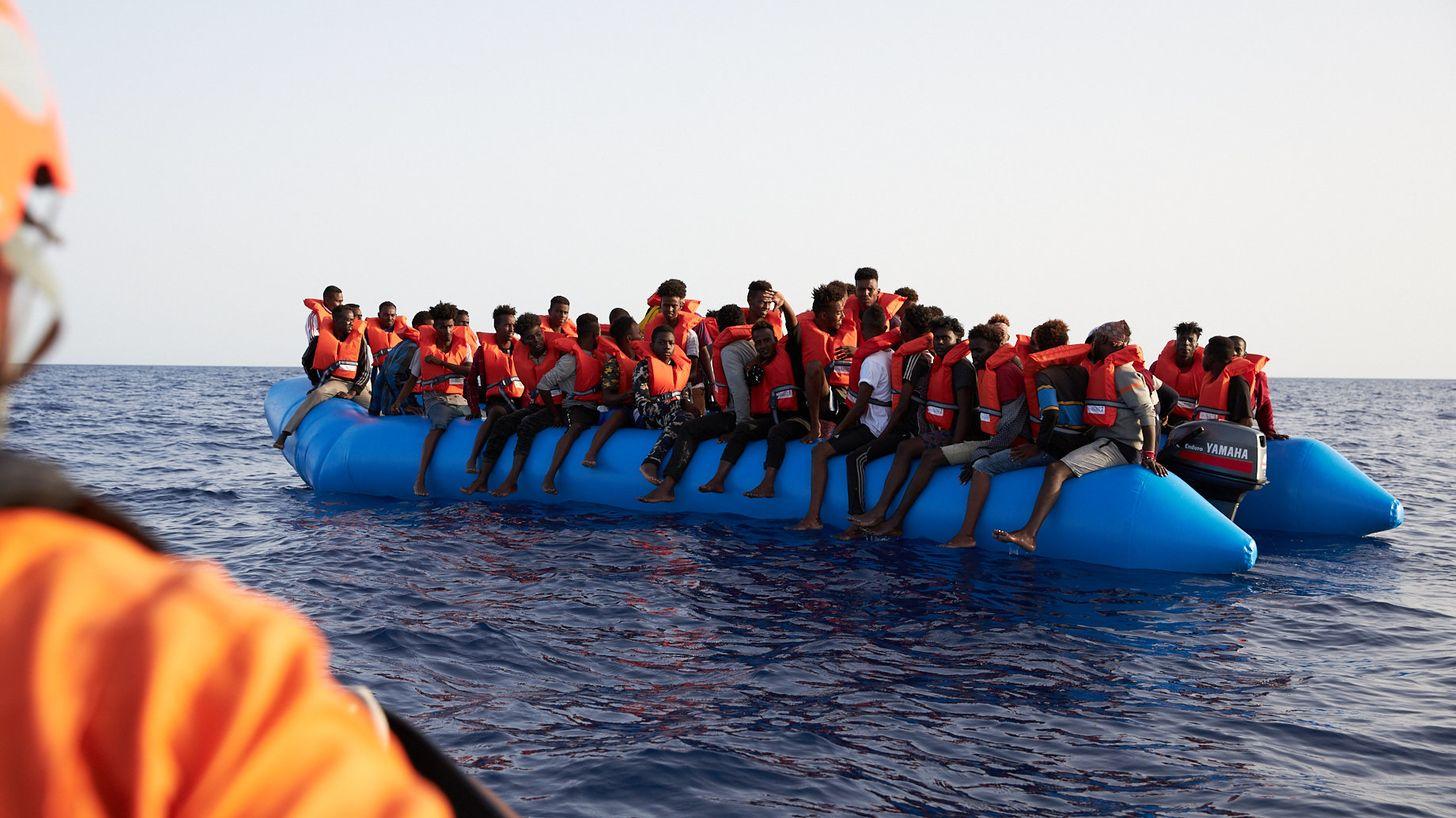 Die von der Seenotrettungsorganisation Sea-Eye herausgegebene Aufnahme zeigt einen Seenotretter (l) der zu einem Flüchtlingsboot schaut.